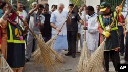 Indian Prime Minister Narendra Modi, center, sweeps an a road with a broom along with civic workers in New Delhi, India, Thursday, Oct. 2, 2014. (AP Photo/Press Trust of India)