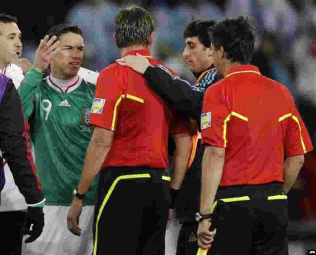Мексики Гильермо Франко (Мексика), спереди слева, спорит с рефери Роберто Розетти из Италии, третий справа, а Диего Милито (Аргентина), второй справа, слушает спор. Матч между Аргентиной и Мексикой на стадионе «Футбол-Сити» в Йоханнесбурге, Южная Африка.