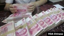 交通銀行沈陽一家分行的一名職員2012年7月6日在點算100圓人民幣的鈔票