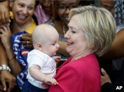 Democratic presidential candidate Hillary Clinton holds a baby as she greets people in the audience at a Pennsylvania Democratic Party voter registration event at West Philadelphia High School in Philadelphia, Aug. 16, 2016.