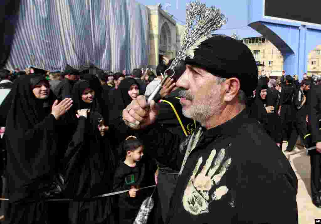 Seorang Muslim Syiah memukuli dirinya dengan rantai sebagai tanda berduka bagi Imam Hussein di antara makam Imam Hussein dan Imam Abbas di Karbala, Irak (13/11). (AP/Hadi Mizban)
