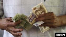 北京一处市场的一名顾客在点算人民币。(2015年8月12日)