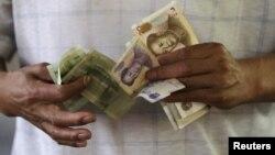 12일 베이징 시장에서 고객이 위안화 화폐를 세고 있다.