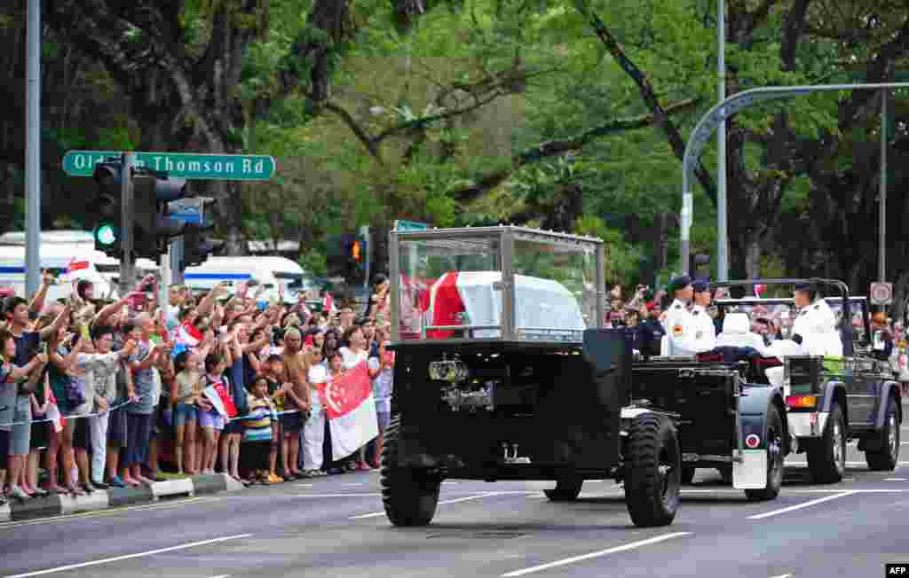 Members of the public react as the ceremonial gun carriage bearing Singapore's late former prime minister Lee Kuan Yew passes by during his funeral procession in Singapore. Tens of thousands of mourners braved torrential rain while howitzers fired a 21-gun salute and jet fighters screamed across the sky as Singapore staged a grand farewell for its founding leader.