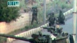 سربازان و یک تانک در خیابانی در شهری که گفته می شود درعا است، استقرار دارند. این تصویر از یک ویدئوی آماتور گرفته شده است - ۲۵ آوریل ۲۰۱۱