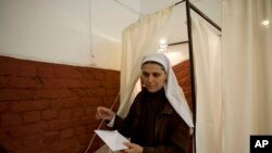 A nun exits a voting booth at a polling station in Budapest during the parliamentary elections in Hungary, Sunday, April 6, 2014.