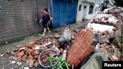 Seorang perempuan berjalan melewati batu bata yang berserakan dan menimpa sebuah mobil, saat sebuah tembok hancur diterjang angin kuat badai Soulik di Taiwan (13/7).