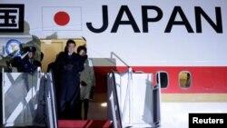 일본 정부 전용기 트랩 위에 선 아베 신조(가운데) 총리와 부인 아키에 여사. (자료사진)