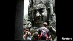 A tourist poses for photographs in the Bayon Temple in the northern province of Siem Reap, about 320 km (199 miles) from Phnom Penh August 31, 2010. Tourist arrivals to Cambodia increased by 14 percent to 1.42 million people, during the first seven months this year as compared to the same period in 2009, said Kong Sophearak, Director of Statistics at the Tourism Ministry. REUTERS/Chor Sokunthea