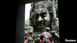 A tourist poses for photographs in the Bayon Temple in the northern province of Siem Reap, file photo.
