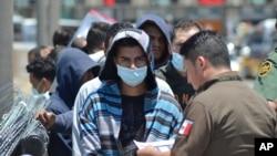 Oficiales de la Patrulla Fronteriza de los Estados Unidos devuelven a un grupo de migrantes de regreso al lado mexicano de la frontera mientras los funcionarios de inmigración mexicanos revisan la lista, en Nuevo Laredo.