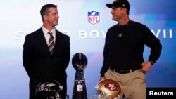San Francisco 49ers head coach Jim Harbaugh (R) and his brother, Baltimore Ravens head coach John Harbaugh, appear at their joint press conference and stand next to the Vince Lombardi trophy ahead of the NFL's Super Bowl XLVII in New Orleans, Louisiana, F
