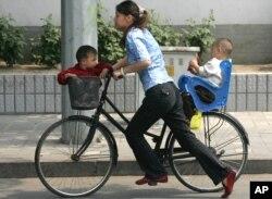 北京一位妇女骑自行车送孩子。