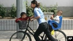 Seorang perempuan China membawa 2 anaknya dengan bersepeda di Beijing (foto: dok). Diperkirakan 1 dari 4 perempuan China mengalami KDRT oleh pasangannya.