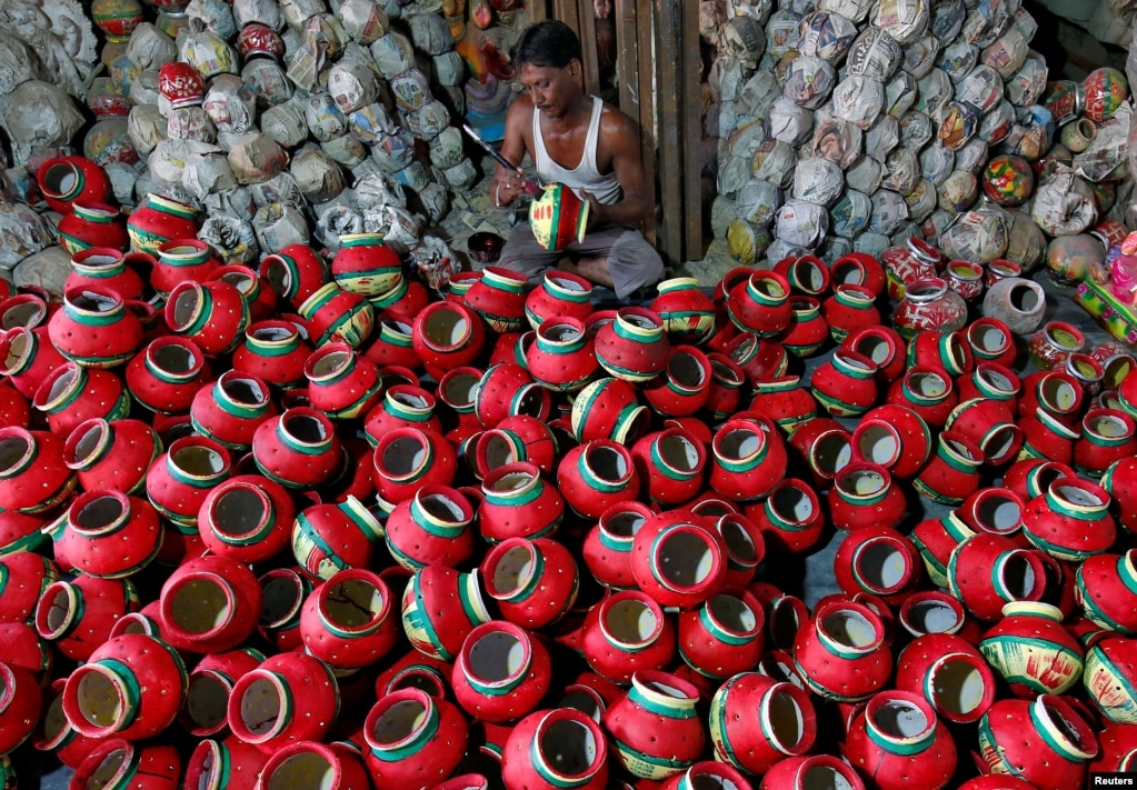 A man cleans a container used during Garba, a folk dance, inside a workshop ahead of Navratri, a festival. During the event, devotees worship the Hindu goddess Durga and young people dance in traditional clothes, in Ahmedabad, India.