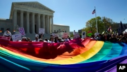 FILE - Demonstrators stand in front of a rainbow flag of the Supreme Court in Washington.