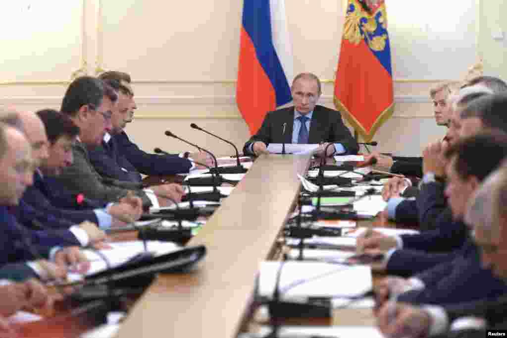 Russia's President Vladimir Putin (C) chairs a government meeting at the Novo-Ogaryovo state residence outside Moscow.