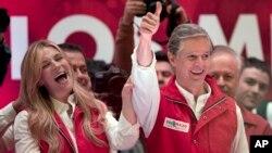 Alfedo del Mazo, candidato del PRI, y su esposa Fernanda Castillo saludan a sus seguidores en Toluca. Del Mazo lleva una leve ventaja en las elecciones para gobernador del Estado de México.