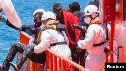 Arhiva - Migrantu, koji je dio grupe od 58 presretnutih na trošnom brodu na oko 100 milja od obale, pomažu spasioci nakon što je stigao u luku Arguineguin, Španija, 30. maja 2016.
