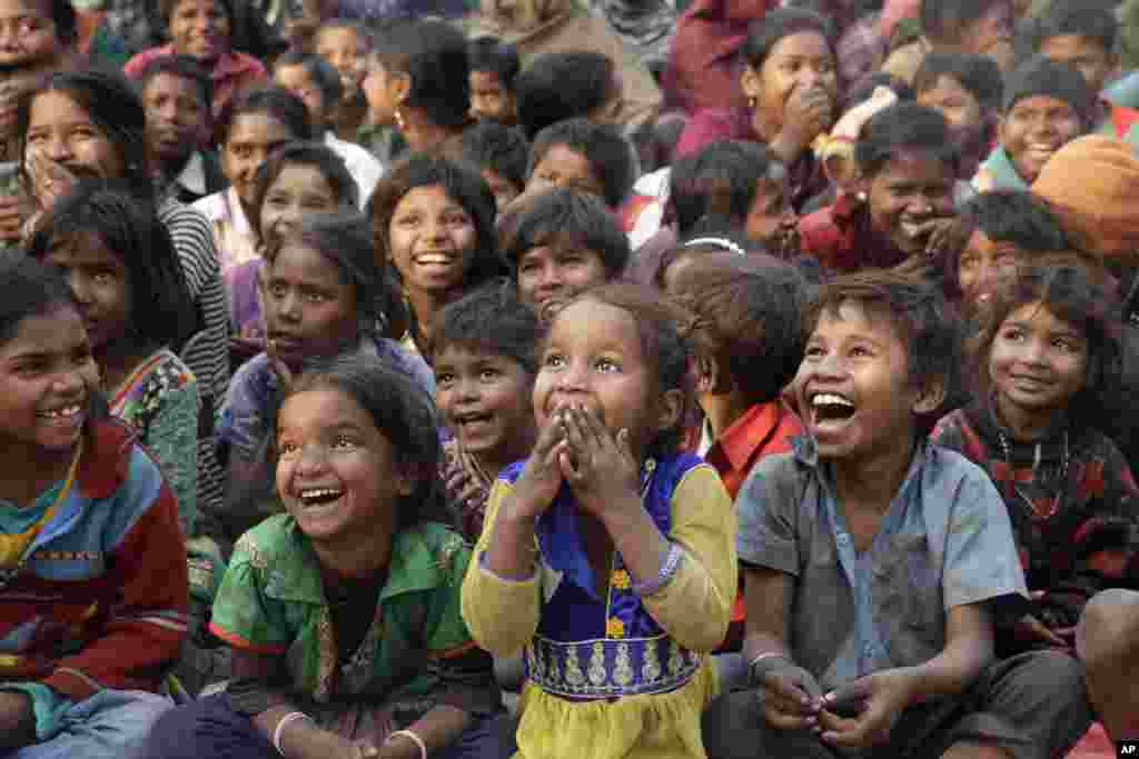 Impoverished Indian children watch a performance that's part of advocacy against child labor, in Allahabad.