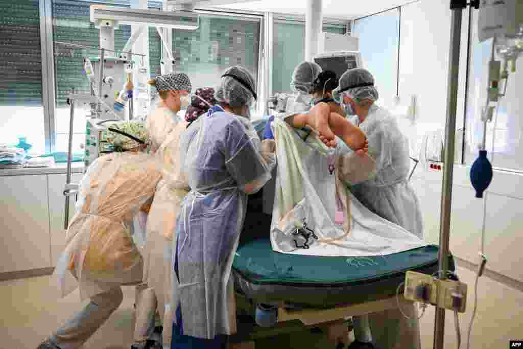 Members of the medical staff hold a patient infected with Covid-19 at the intensive care unit of the Andre-Gregoire intercommunal hospital, in Montreuil, Seine-Saint-Denis, on the outskirts of Paris, France.