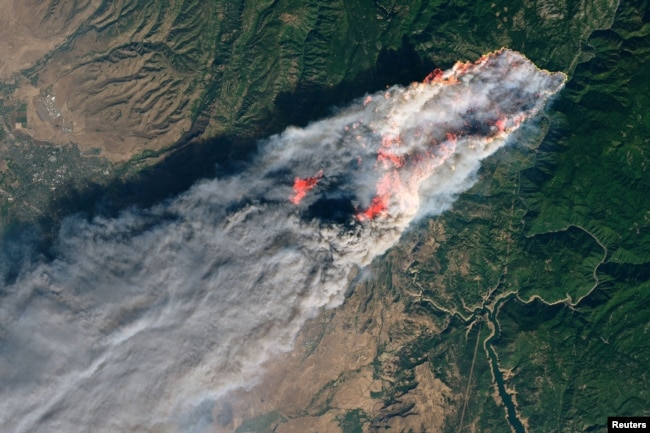 FILE - NASA's Operational Land Imager satellite image shows the Camp Fire burning at around 10:45 a.m. local time near Paradise, California, Nov. 8, 2018.