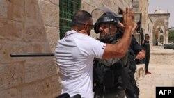 İsrailli bir asker Mescid-i Aksa girişinde Müslüman bir Filistinli'nin üzerini arıyor.