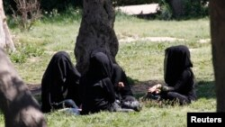 FILE - Veiled women sit in a garden in the northern province of Raqqa, Syria, March 31, 2014. The Islamic State has imposed strict new dress codes on women.