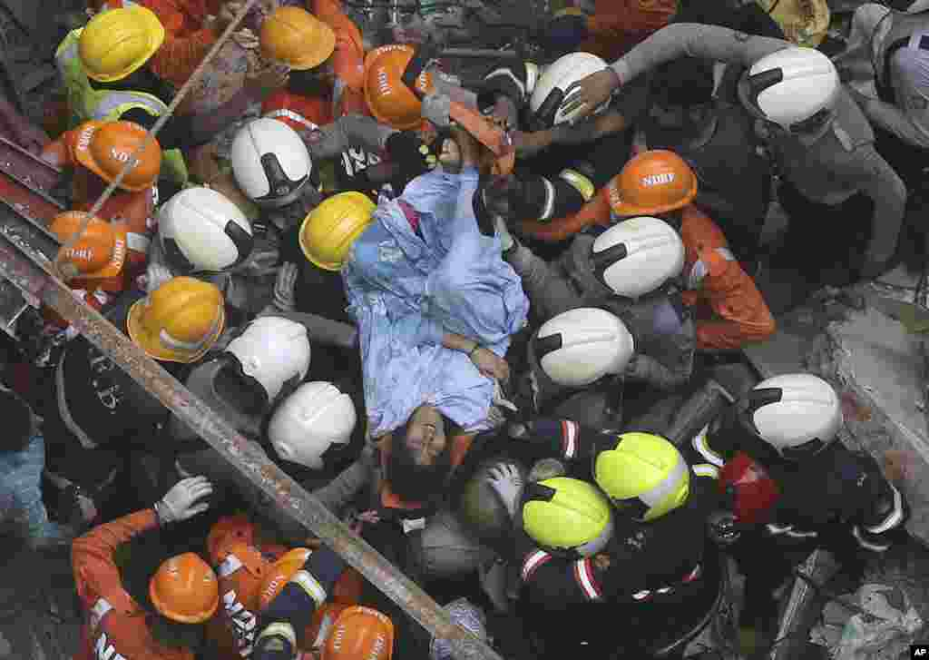 Rescuers carry out a survivor from the site of a building that collapsed in Mumbai, India. A four-story residential building collapsed in a crowded neighborhood and several people were feared trapped in the rubble, an official said.