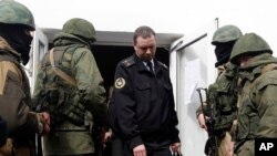 """Rus əsgərləri olduqları güman edilən uniformasız """"yaşıl adamlar""""-ın əhatəsində ukraynalı donanma zabiti Krımdakı hərbi bazanı tərk edir."""