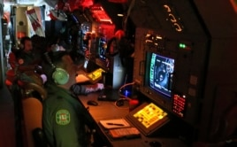 Aircrew man radars and sonar on board a Royal Australian Air Force AP-3C Orion as they search for the missing Malaysia Airlines Flight MH370 in southern Indian Ocean, Australia, Mar. 22, 2014.