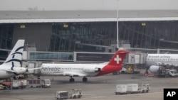 Mobil pengangkut bagasi melewati sebuah pesawat milik maskapai Helvetic Airways. Berlian bernilai sedikitnya 50 juta dolar dilaporkan dicuri di bandara Internasional Brussels ini (19/2).