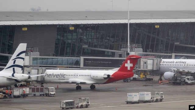 Baggage carts make their way past a Helvetic Airways aircraft from which millions' of dollars worth of diamonds were stolen on the tarmac of Brussels international airport, February 19, 2013.