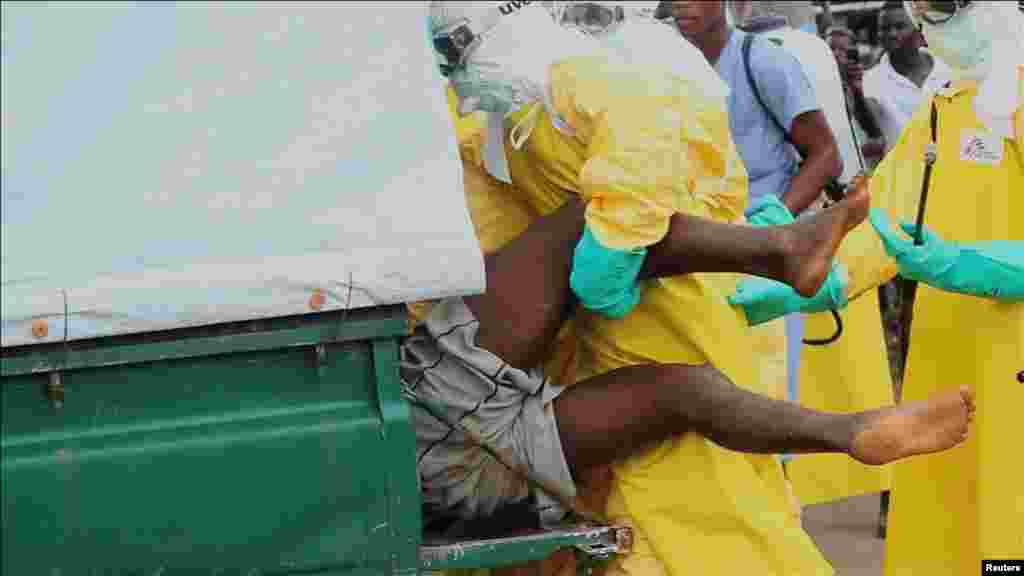 Health workers capture an Ebola patient who escaped from quarantine at the Elwa Hospital, Paynesville, Liberia, Sept. 1, 2014.
