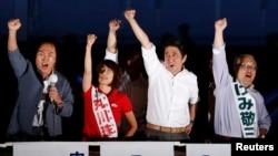 PM Jepang Shinzo Abe (dua dari kanan), dan para pemimpin partai Liberal Demokrat yang berkuasa (LDP) mengepalkan tangannya untuk memberikan semangat kepada para pendukungnya dalam kampanye pemilu parlemen di Tokyo, Jepang (20/7).