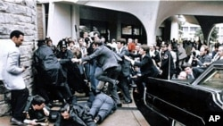 Former White House press secretary James Brady, face down at right, and Washington police officer Thomas Delahanty, front, lie on the ground after being wounded during the assassination attempt on President Reagan as he was leaving a hotel in Washington (