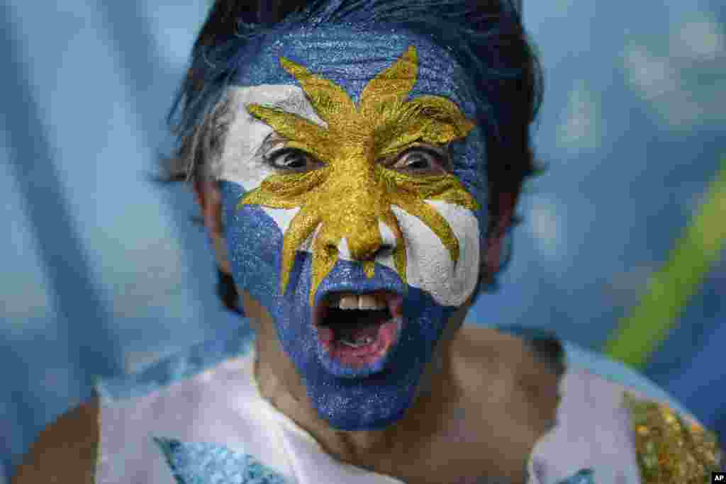 An Argentina soccer fan cheers outside the Maracana Stadium before the group F World Cup soccer match between Argentina and Bosnia, in Rio de Janeiro, Brazil, June 15, 2014.