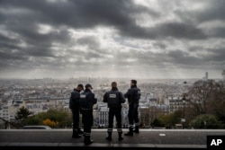 The city of Paris stretches out before French police officers as they stand guard near the church of Sacre Coeur, on top of the Montmartre hill, Nov. 18, 2015.