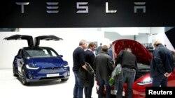 Visitors inspect Tesla electric cars at Brussels Motor Show, Belgium, Jan. 18, 2019.