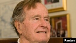 FILE - Former President George H.W. Bush, pictured in Houston in March 2012 at a Mitt Romney speech, is working to regain strength amid a bout with pneumonia.