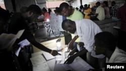 Electoral workers revise ballot papers during vote counting in Port-au-Prince, Haiti, August 9, 2015.
