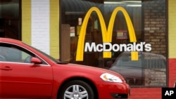 FILE - A car is seen moving through a McDonald's drive-through window line, in Springfield, Illilois.