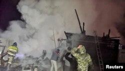 Petugas pemadam kebakaran dan penduduk lokal berupaya memadamkan kebakaran di rumah jompo di desa Ishbuldino, Rusia, 15 Desember 2020. (Kementerian Darurat Rusia / Selebaran via REUTERS)