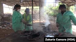 Mariam Keita, directrice de 'Binedou Global Service', et deux de ses employées remplissent les moules, à Conakry, le 5 février 2019. (VOA/Zakaria Camara)