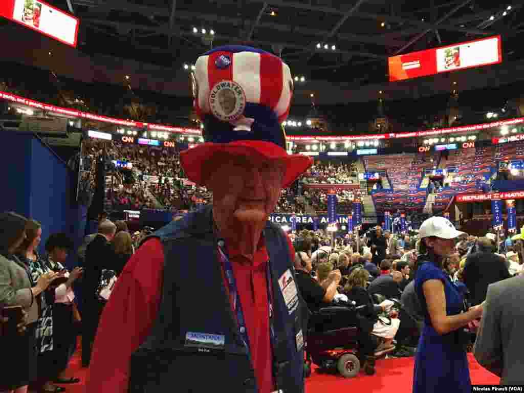 Couvert d'un chapeau rappelant l'oncle Sam, un participant affiche des insignes de l'état de Montana et de l'ancien président Bush à Cleveland, Ohio, le 18 juillet 2016. (VOA/Nicolas Pinault).