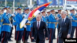 Russian President Vladimir Putin (L) and Serbian President Tomislav Nikolic walk in front of a honor guard in front of the Serbia Palace building in Belgrade Oct. 16, 2014.
