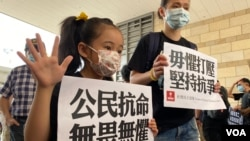 有家長帶同年幼的女兒到法庭外聲援15名被控非法集結等罪名的民主派人士。(美國之音湯惠芸)