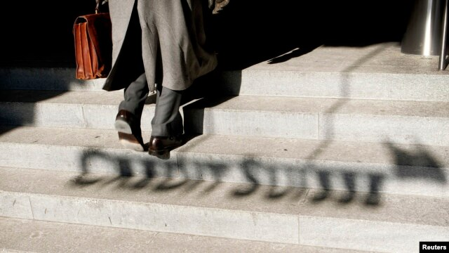 FILE - A man walks past the shadow of the logo of Swiss bank Credit Suisse in Zurich.