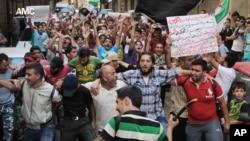 "Pengunjuk rasa anti rejim Suriah dalam demonstrasi di Aleppo (6/9). Poster dalam bahasa Arab itu berbunyi,""DK PBB, lihatlah! Perempuan dan anak-anak yang menjadi korban akan membawa konflik ini ke Pengadilan Tuhan"" (AP Photo/Aleppo Media Center, AMC)"