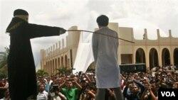Seorang polisi Syariah mencambuk seorang laki-laki yang terbukti melakukan perzinaan di Jantho, Aceh (foto: dok).